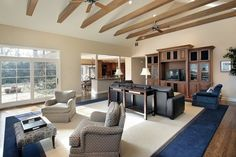 A great room with two designated seating areas separated by a single side table behind the leather sofa. The room's seating is divided between a formal seating area and a media center. Both seating areas are on the blue and cream area rug, which helps unite the two spaces.