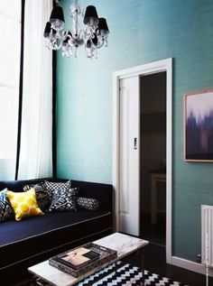 colors! black couch yellow pillow black and white rug blue walls