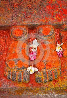 Pair of sculptured feet covered with red substances and flowers symbolising deity in hindu temple