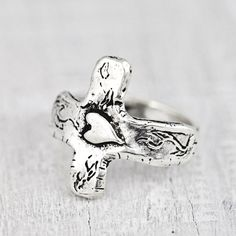 Handcrafted cross ring with a tiny heart in the middle wraps around your finger. Discover more of our faith inspired jewelry.