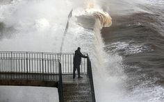 Feb 2014, The high winds and heavy showers will ease throughout Wednesday, but Thursday night and into Friday morning we will see up to 25mm of rain coming in the South West and southern counties. Here, a man watches the raging sea from Dawlish station's soaked railway bridge. Lines into Cornwall are in jeopardy.