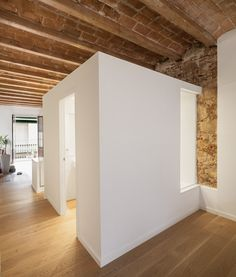 Barcelona architect Sergi Pons has exposed stone walls and wooden beams during the renovation of this apartment in the city's Les Corts district.