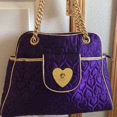 """Betsey Johnson Purple Satin Tote This bag is the perfect catch all.  Measuring 16.5"""" wide and 12"""" tall, it's the perfect glam tote.  In good (not great) condition, included photos that show some snags on satin stitching and scratches gold heart.  Spacious and zips!  Great front pocket for cell phone and keys. Betsey Johnson Bags Totes"""