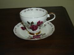 """Cup and saucer set in the Persian Rose design, gold accenting  The cup is 2 15/16"""" (7.5 cm) high x 3 7/16"""" (8.7 cm) at the brim and the saucer is 5 7/16"""" (13.8 cm) in diameter  There is some wear (+/- 5%) of the gold on the brim but otherwise this set is in very good condition and only appears to have seen use as a collectible  Made of fine bone china from England by Adderley    These items have no nicks, chips, cracks, or signs of repair 