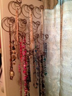Old bed springs repurposed or upcycled into a jewelry / necklace organizer. Quick and easy organization project to do. My bed springs were rusty, so I sprayed them with polyurethane to seal in the rust. Then, I just put a nail where I wanted the bed spring to go and hung the bed spring on it. I did off center each row of springs so that the necklaces hung freely.