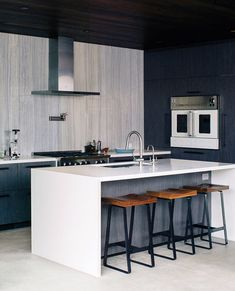 """@dwellmagazine: """"In the kitchen Walker continued an earthy color scheme. The range and wall oven are by BlueStar the hood is from Zephyr and the island is Caesarstone. Photo by @jose_mandojana . Architecture by Walker Workshop Design Build. #kitchen #interior"""""""