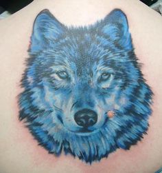 Realistic 3d blue wolf face tattoo on upper back