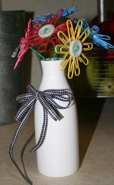 """A little hot glue for the paper clips onto the button centers, a little vase lying around the house... Fill bottom of vase with a filler, add paper clip flowers and surprise the kids when they wake up and see their """"flowers"""" on their nightstands."""