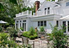 White traditional home, roof deck over sunroom, balcony, white railing