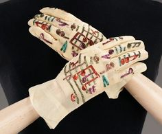 Gloves from Elsa Schiaparelli evening dress, 1939. The musical notes and symbols are embroidered in vibrant metallic thread on a gossamer organza.