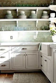 I like the white open shelves with simple corbels paired with the glassy backsplash tile