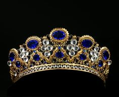 A tiara, probably for the statue of a Virgen. Gilt metal embellished with numerous blue and clear glass cabochons. 1850-1870. Width : 5 1/8 inch Height : 2 3/4 inch Depth : 5 1/8 inch