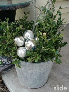 Greenery with silver ornaments tucked into a galvanized bucket.