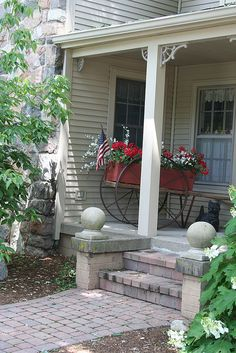 Porch with flag and wagon of red and white...