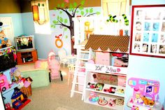 """I know this looks overwhelming, but when you scroll through the pics of this playroom it's got """"boy"""" and """"girl"""" spaces and it's very cute and family oriented.  We could put Maddie's kitchen area under a little awning like that!"""