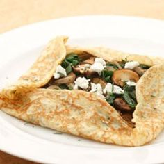 Savory Crepes for brunch, lunch and even dinner! Try these crepes, filled with spinach and meaty mushrooms and topped with crumbled goat cheese, for a light supper with a salad on the side.