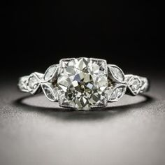 A bright and shining European-cut diamond, weighing one-and-a-third carats, beams brilliantly with a bright sunshiny glow between sparkling white diamond leaves set with small marquise and round diamonds in this stunning vintage engagement ring hand fabricated in gleaming 18K white gold, circa 1920s-30s. A delightfully distinctive Art Deco dazzler. Currently ring size 6.