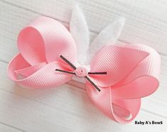 A new Easter/Spring piece for 2015! This absolutely adorable pink and white bunny bow is sure to be loved by your little one and everyone else as well! Cute felt ears and a little ribbon nose with whiskers make this piece special.  Measuring approximately 4 across, the bow is made with a 7/8 light pink boutique bow. A 3/8 white grosgrain ribbon is wrapped around the center of the bow. Attached to the bow are skinny, white felt ears, and in the center is a light pink ribbon nose and skinny…