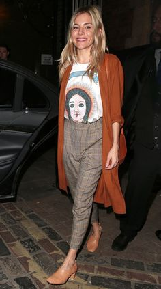 Sienna Miler in a graphic t-shirt, plaid pants and long sweater