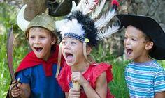 Three children in fancy dress playing.
