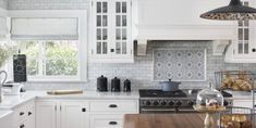 A hand-painted, Carrara marble backsplash contrasts with subway tile in this kitchen from Lisa Michael Interiors.