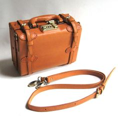 Mini suitcase designer leather handbag by Camden Leatherworks. With double outside webbing straps and combination lock. Protective studs on base. Fully lined with internal organiser pockets.  SIZE >> 25 x 20 x 12 cm [small!]