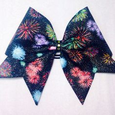 Large fabric cheer bow with fireworks and gold glitter accents.