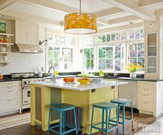 A cheerful yellow island creates a youthful energy in this sunny kitchen. A dramatic coffered ceiling also adds architectural interest overhead. A combination of open shelving and ribbed-glass cabinet fronts blends with the openness created by the large bank of windows.