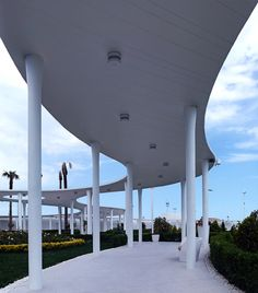 A curving concrete canopy supported by hundreds of columns loops around the perimeter of this renovated beach club.