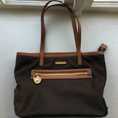 Michael Kors purse Beautiful gently used Michael Kors purse. Metallic dark brown with light brown and gold accent. This is a great summer/winter purse. Main bag zips, four interior pockets perfect for phone, lip gloss, keys, etc. Inner zip pocket. Michael Kors Bags Shoulder Bags