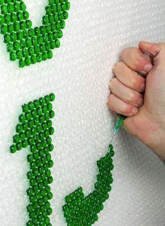Plástico bolha pendurado na parede e injetado com fluídos coloridos para criar letras. Weird Magazine, do Reino-Unido.
