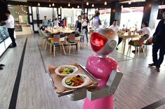 A robot waitress delivers meals for customers at robot-themed restaurant on May 18, 2015 in Yiwu, Zhejiang province of China.  (Image source: ChinaFotoPress via Getty Images)