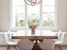 Contemporary dining room features a rope sphere chandelier hanging over a square wood dining table with glass top lined with Eames Molded Plastic Armchairs.