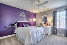 Bedroom with purple accent wall and sand color walls with light carpet