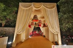 large temple bells, floral temple bell entrance white draped entrance, elegant entranceway, orange and white decor