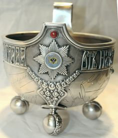 Fabergé silver military presentation kovsh, circa 1909, given to a senior Russian National Guard commander of the Warsaw squadron, featuring engraved signatures of fellow officers. With traditional Russian decoration, bezel-set jewels, four spherical feet and a blue enameled double-headed eagle military emblem.