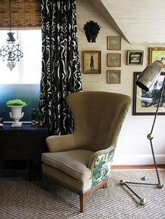 eclectic corner with matchstick blinds, dramatic black and white curtains and wing chair