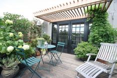 A terrace garden in Chelsea featuring custom-designed planter beds intermixed with pots of varied shape and size. Cafe chairs and table and a beach chair add to the eclectic setting.