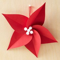 Paper Poinsettia Ornament - To make, cut the cardstock into five small tear-drop shapes. Fold each in half lengthwise and crease, then unfold. Using hot glue, adhere the round ends to create the flower center. Finish by bedazzling with mini white pom-poms.