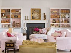 Pink and Gold Room--Pink can be the perfect neutral tone for an interior, and when partnered with gold, it assumes a classical air. Pink vintage wallpaper lines the bookshelves in this living room, which were then filled gold and silver collection pieces. An antique gilded picture frame balances the gold silk taffeta chair across the room. The Chinese lacquer table grounds the pink and white furnishings..