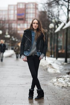 Octavia cross-legged in layers: a shearling motorcycle jacket, denim jacket, sweater, and striped top over black skinny jeans and sneakers.