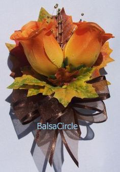 corsage idea, burnt orange flower with fall leaves and brown bows. Could add berries for mothers and groom