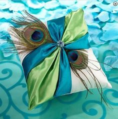 """Measuring 7"""" x 7"""", this elegant ring pillow is covered in cream satin. The front is decorated with a green and teal satin sash, two peacock feathers and a rhinestone ornament. The ornament combines li                                                                                                                                                                                 More"""
