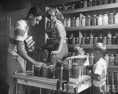 A 1950s woman and her family putting up an assortment of canned fruits and vegetables. #vintage #canning #homemaker