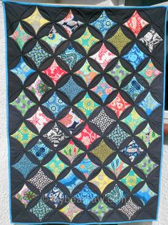 """Amy Butler's """"Lark"""" fabric combined with Kona Charcoal. I'd been thinking I'd use some sort of white to go with mine, but this has me reconsidering; the colorful Lark fabrics really pop against the dark fabric!  myBearpaw: Jumbo Cathedral Window Quilt"""