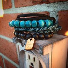 This pack of bracelets features one Teal and black triple wrap paracord bracelet. one adjustable paracord bracelet. and two wood beaded stretch bracelets. Products are handmade in the USA.
