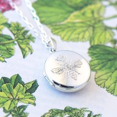 A stunning and beautifully engraved silver locket necklace by jewellery designer and maker Heather Scott.  This dainty, quirky and beautiful bee necklace would make a perfect present for a loved one (or bee enthusiast!) or a treat for yourself! The silver locket has a beautiful engraving of a bee topped off with a crown. Open the locket, and you can put a picture of whoever you like inside!  Gift wrapping is offered for free, however the necklace comes in a blue box. I hope that you like my…