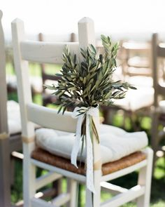 Inspired by the area's olive groves, the couple decorated ceremony seats with bundles of leaves from the trees. More