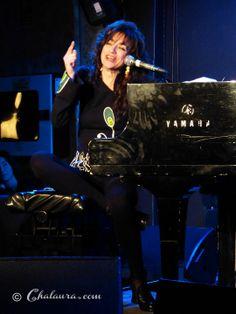 Carmen París sentada al piano mientras canta alzando la mano derecha