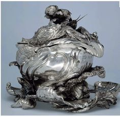 A silver soup tureen wrought in the form of a shell with a fluted lid covered with realistic putti, crayfish and vegetables, circa 1735–1740, was made by Henri-Guillaume Adnet and Francois Bonnestrenne under the direction of Juste-Aurèle Meissonier, the Turin-born master goldsmith as reported by Antiques and the Arts Online.